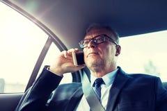 Uomo d'affari senior che rivolge allo smartphone in automobile immagini stock libere da diritti