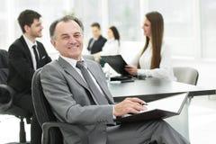Uomo d'affari senior con una lavagna per appunti sui precedenti dell'ufficio fotografia stock libera da diritti