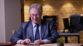 Uomo d'affari senior in costume convenzionale che scrive sulla compressa che ? attenta e concentrata in ufficio archivi video