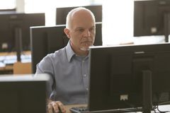 Uomo d'affari senior dedicato che lavora ad un desktop fotografia stock