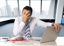 Uomo d'affari senior disperato nella crisi che lavora al computer portatile del computer alla scrivania nello sforzo sotto pressi fotografie stock libere da diritti