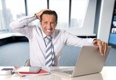 Uomo d'affari senior disperato nella crisi che lavora al computer portatile del computer alla scrivania nello sforzo sotto pressi fotografia stock libera da diritti