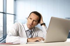 Uomo d'affari senior disperato nella crisi che lavora al computer portatile del computer alla scrivania nello sforzo sotto pressi immagine stock libera da diritti
