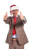 Uomo d'affari senior felice che porta il cappello del Babbo Natale che fa segno giusto fotografie stock libere da diritti