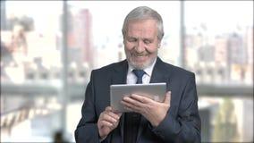 Uomo d'affari senior felice con la compressa del pc video d archivio