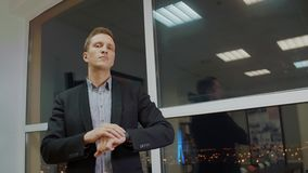 Uomo d'affari serio bello che regola il suo orologio vicino alla finestra in ufficio archivi video