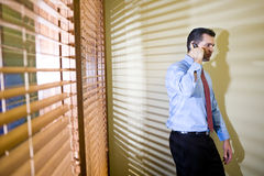 Uomo d'affari serio che comunica sul telefono mobile Fotografie Stock