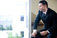 Uomo d'affari serio che osserva fuori la finestra dell'ufficio Fotografia Stock