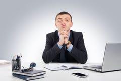 Uomo d'affari serio che vi esamina scettico che vi sedete al suo de Immagine Stock Libera da Diritti