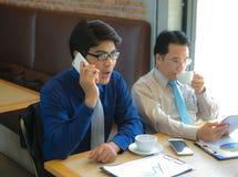 Uomo d'affari serio due facendo uso del telefono del moblie fotografie stock libere da diritti