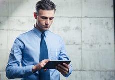 Uomo d'affari serio facendo uso del computer della compressa Immagini Stock