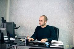 Uomo d'affari serio facendo uso del computer nel suo ufficio immagine stock
