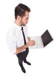 Uomo d'affari serio facendo uso del suo computer portatile Fotografie Stock