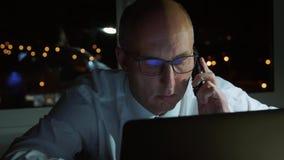 Uomo d'affari serio facendo uso del telefono cellulare per la conversazione di affari in ufficio scuro video d archivio