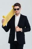 Uomo d'affari serio in occhiali da sole che tengono pattino giallo sulla sua spalla Fotografia Stock Libera da Diritti