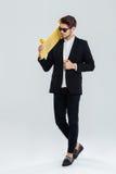 Uomo d'affari serio in occhiali da sole che tengono pattino giallo sulla sua spalla Immagine Stock