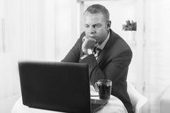Uomo d'affari serio, testa degli impianti nell'ufficio, tavola di seduta, sguardi intento ad un computer portatile Foto in bianco Immagine Stock