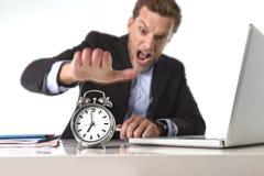 Uomo d'affari sfruttato alla scrivania sollecitata e frustrata con la sveglia dentro dal concetto di termine e di tempo Fotografia Stock