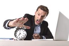 Uomo d'affari sfruttato alla scrivania sollecitata e frustrata con la sveglia dentro dal concetto di termine e di tempo Immagini Stock Libere da Diritti