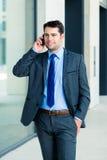 Uomo d'affari sicuro all'aperto facendo uso del telefono fotografia stock libera da diritti