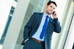 Uomo d'affari sicuro all'aperto facendo uso del telefono immagine stock