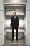 Uomo d'affari sicuro With Briefcase Standing in elevatore immagine stock