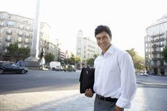 Uomo d'affari sicuro With Briefcase Standing sulla via della città fotografie stock libere da diritti