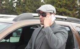 Uomo d'affari sicuro che discute a fondo il fon mobile Immagine Stock