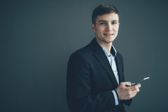 Uomo d'affari sicuro che pende contro una parete mentre per mezzo dello smartphone sul fondo nero Immagine Stock