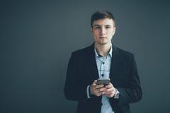 Uomo d'affari sicuro che pende contro una parete mentre per mezzo dello smartphone sul fondo nero Fotografie Stock