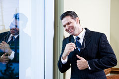Uomo d'affari sicuro che si leva in piedi nell'ufficio dalla finestra Immagine Stock Libera da Diritti