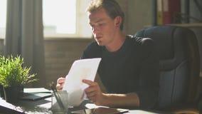 Uomo d'affari sicuro che si siede nell'ufficio moderno per spiegare lavoro ai membri Grafico finanziario di affari con i diagramm stock footage
