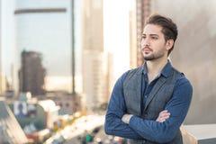 Uomo d'affari sicuro che sta sulla cima della città con fotografia stock