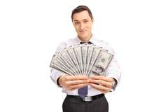 Uomo d'affari sicuro che tiene una pila di soldi Fotografie Stock Libere da Diritti