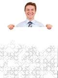 Uomo d'affari sicuro che tiene una scheda bianca di puzzle Fotografie Stock