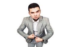 Uomo d'affari sicuro di sé Il giovane tipo barbuto alla moda in un vestito grigio mostra il suo bicipite fotografia stock