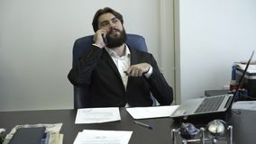 Uomo d'affari sicuro e riuscito che parla sul telefono e che si siede su una sedia Trattative di affari video d archivio