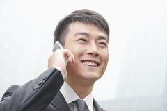 Uomo d'affari sicuro e sorridente sul suo telefono cellulare all'aperto a Pechino, Cina Fotografia Stock