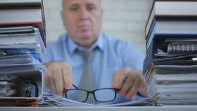 Uomo d'affari sicuro With Eyeglasses Working nella stanza dell'archivio di contabilità fotografia stock