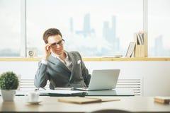 Uomo d'affari sicuro facendo uso del computer portatile Immagini Stock Libere da Diritti