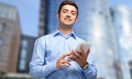 Uomo d'affari sicuro facendo uso della sua compressa Immagini Stock