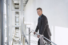 Uomo d'affari sicuro Standing By Railing Fotografie Stock