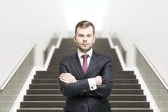 Uomo d'affari sicuro sulla parte anteriore della scala Fotografia Stock