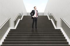 Uomo d'affari sicuro sulla scala Fotografie Stock Libere da Diritti