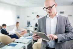 Uomo d'affari sicuro Using Tablet Computer in ufficio fotografia stock