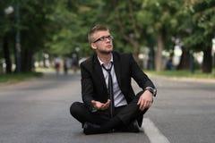 Uomo d'affari Sitting On Asphalt Begs For Money Immagini Stock Libere da Diritti