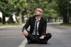 Uomo d'affari Sitting On Asphalt Begs For Money Fotografia Stock Libera da Diritti