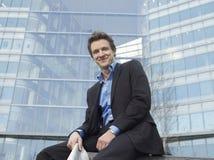 Uomo d'affari Sitting In Front Of Office Building Immagini Stock Libere da Diritti
