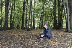 Uomo d'affari Sitting With Laptop su terra in foresta fotografie stock