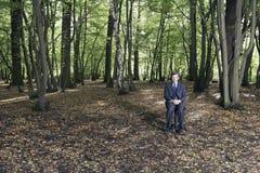 Uomo d'affari Sitting In Middle della foresta fotografia stock